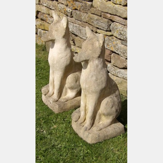 A pair of weathered stone foxes
